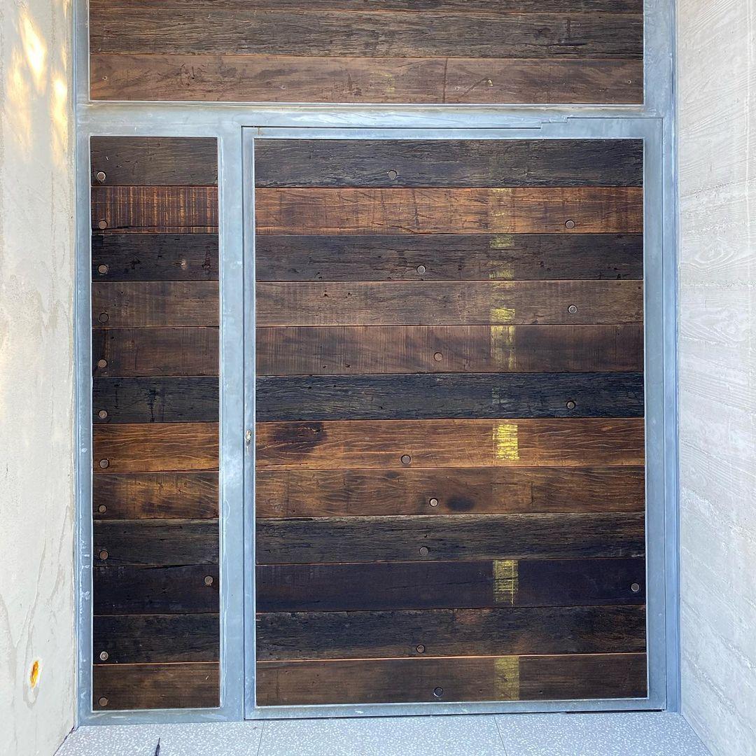 Habillage mural et porte d'entrée en planches fond de wagon sncf.
